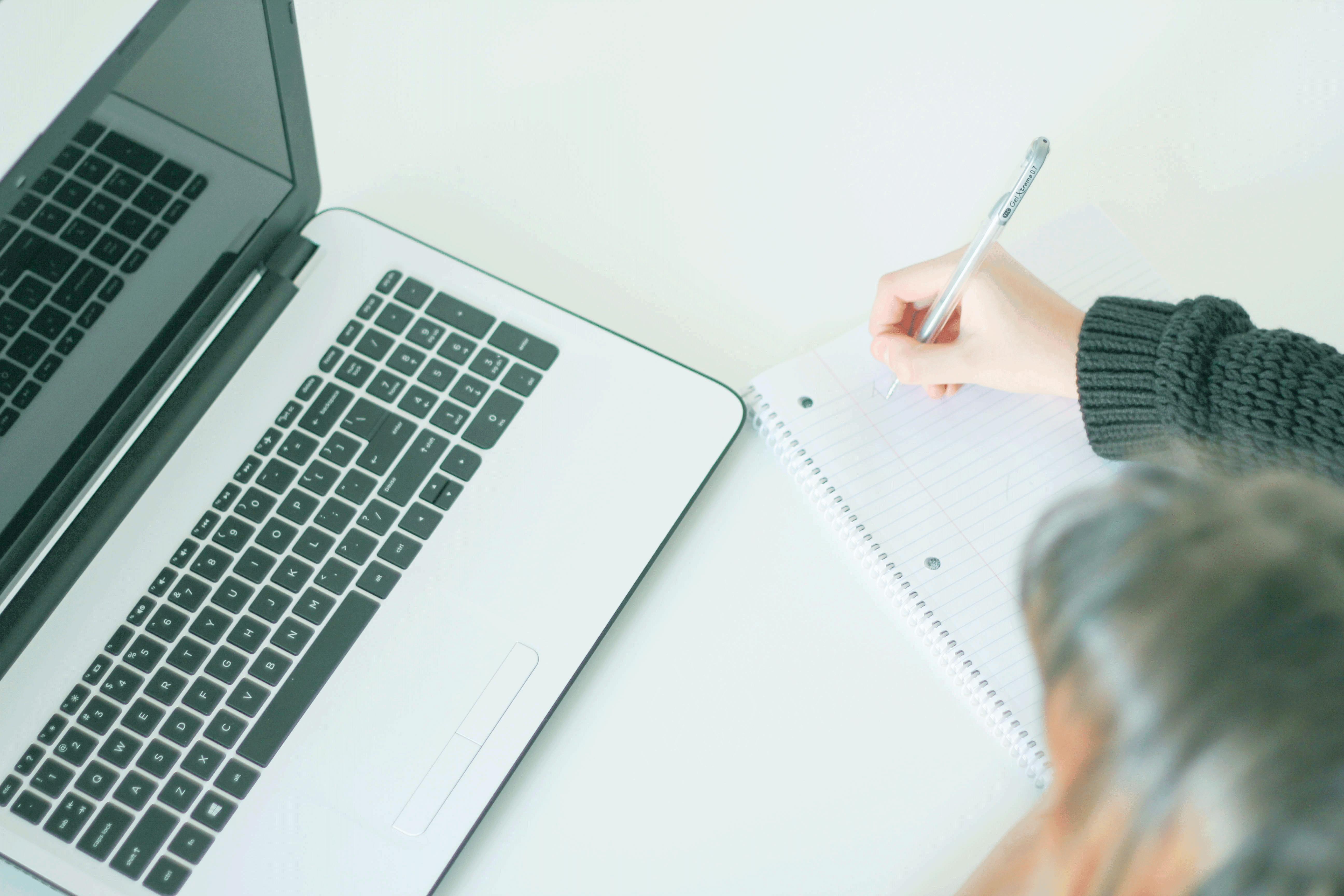 Vrouw noteert in notitieblok achter haar computer