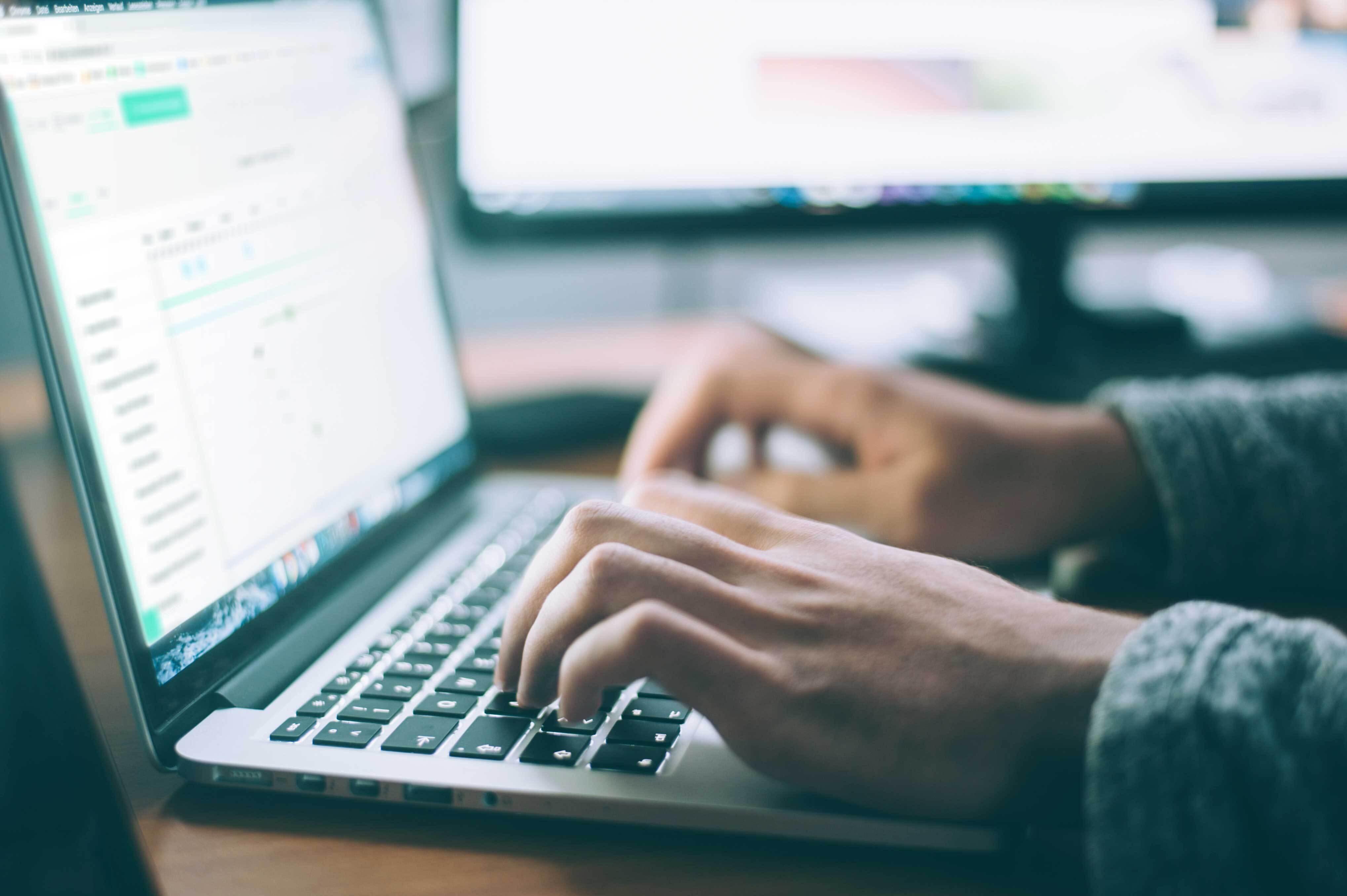 Twee handen gebruiken het toetsenbord van een laptop. Op de achtergrond staat er een tweede beeldscherm.