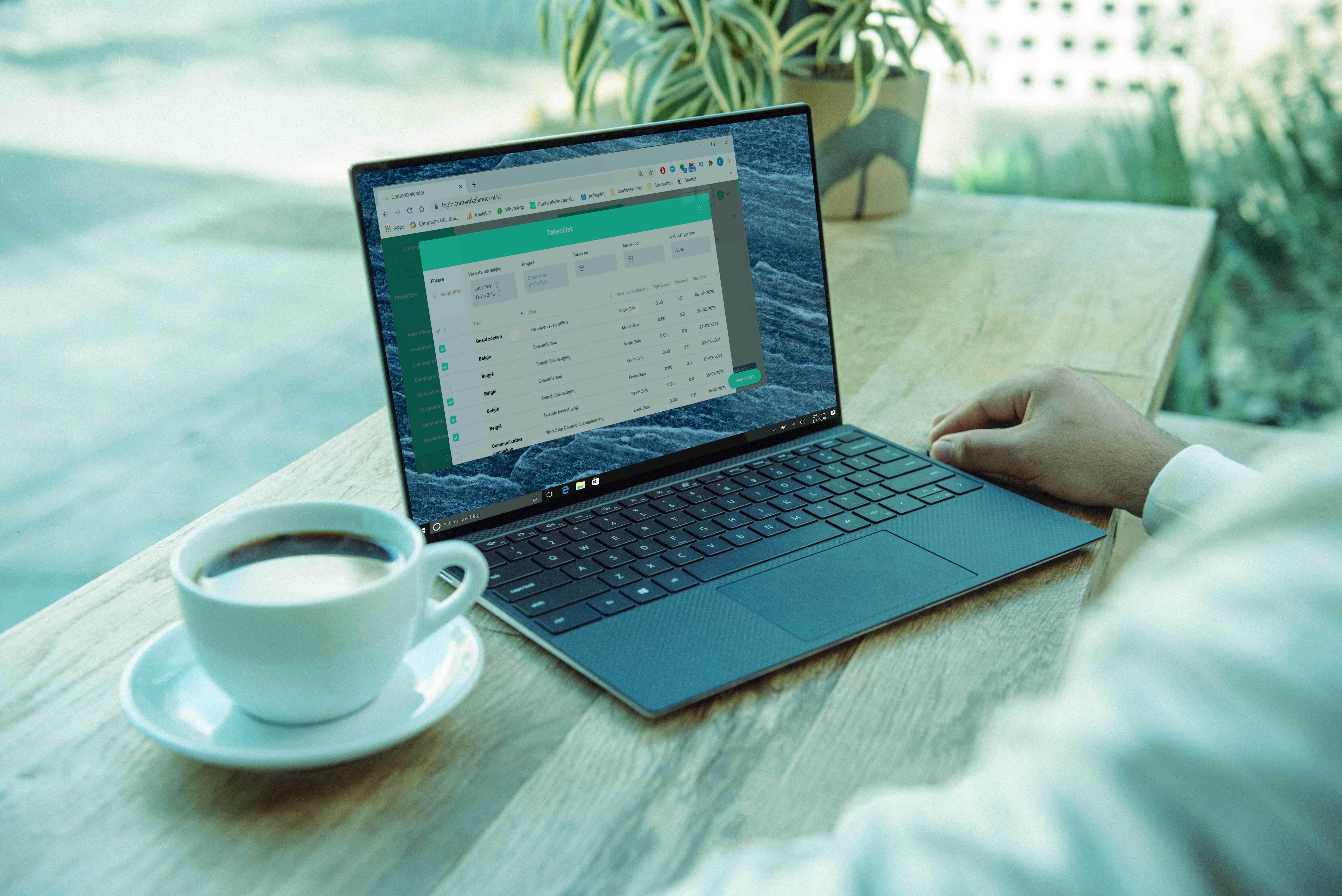 Persoon zit achter bureau met daarop kopje koffie en laptop met de Contentkalender open