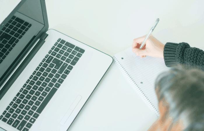 Vrouw noteert iets in een notitieblok met haar laptop voor zich