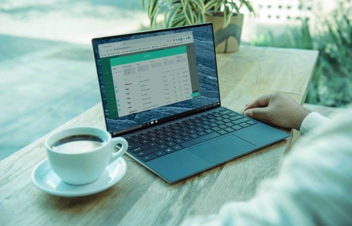 Persoon zit achter bureau met daarop kopje koffie en laptop met de Contentkalender open.